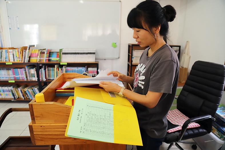 #독서기록장을 보여주는 000 선생님. 개인별 독서 기록을 모두 관리하고 있고 연령대에 맞는 교재를 제공한다.