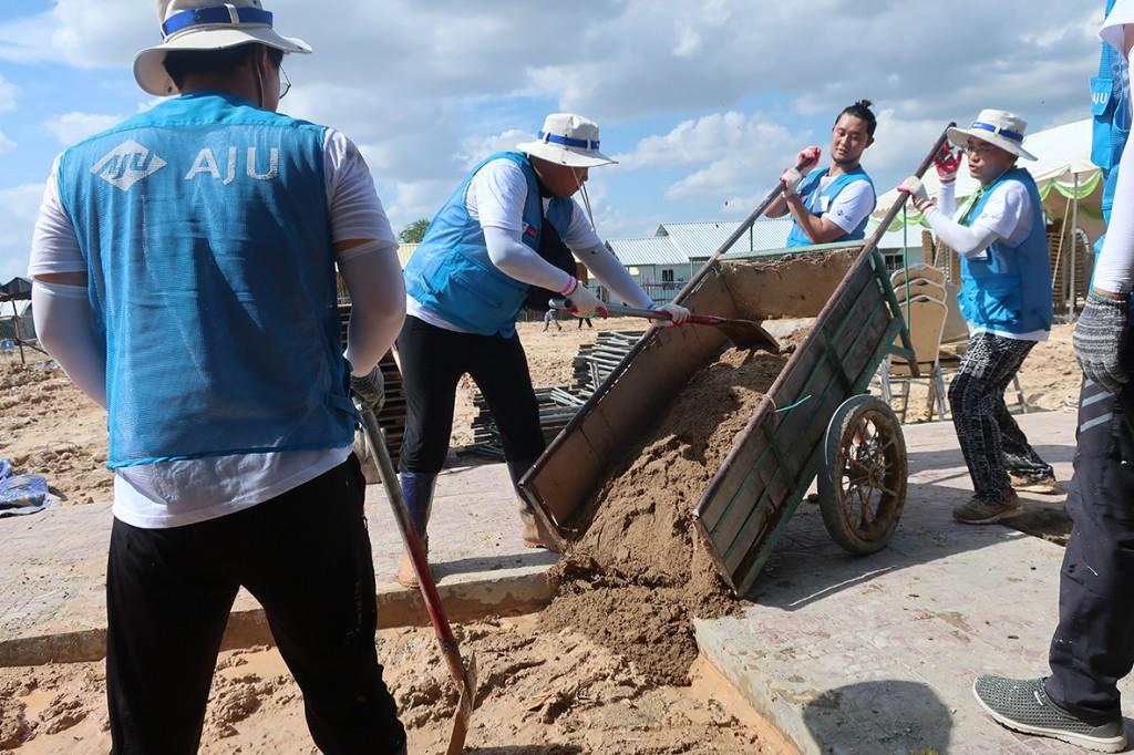 #아주봉사단원들이 폭우로 엉망이된 땅을 다지는 노력봉사를 실시하고 있다.
