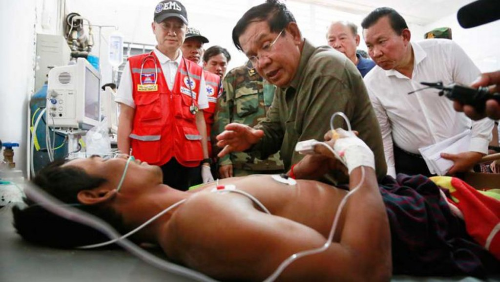 Prime Minister Hun Sen visits a victim retrieved from the debris of a six-storey building collapse in Kep province.