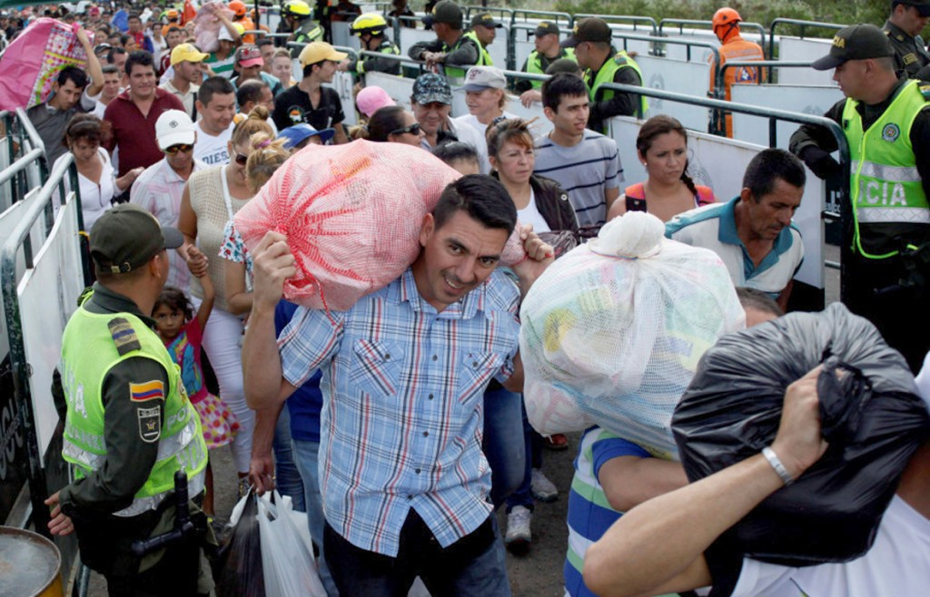 People are seen carrying bags and packages as they cross the Colombian-Venezuelan border over the Simon Bolivar international bridge after shopping in Cucuta, Colombia