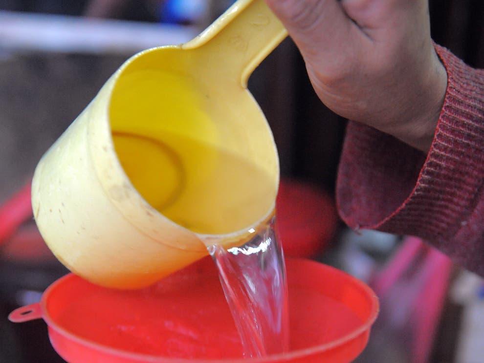 ▲ 한 캄보디아 여성이 발효주를 판매하기 위해 용기에 담고 있다.
