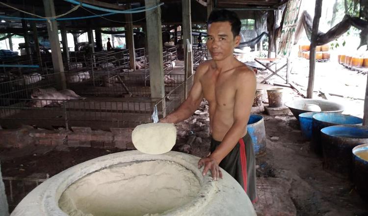 돼지 먹이로 쓰는 쌀가루를 보여주는 양돈업자 겸 주조업자