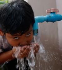 2021-06-08 한 캄보디아 아이가 새로 연결된 상수도관에서 나오는 수돗물을 마시고 있다