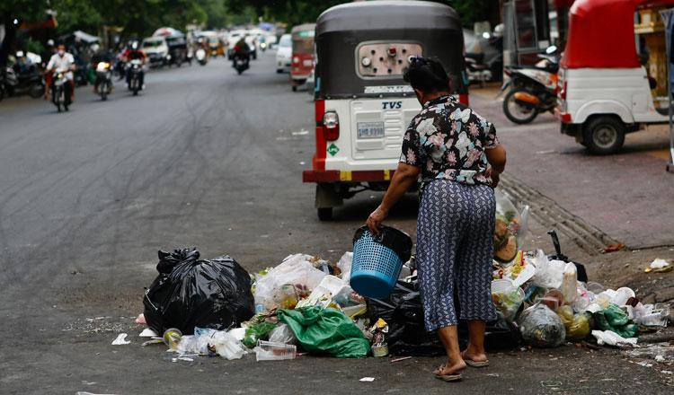▲ 프놈펜의 한 여성이 정해진 수거장소에 쓰레기를 버리고 있다.