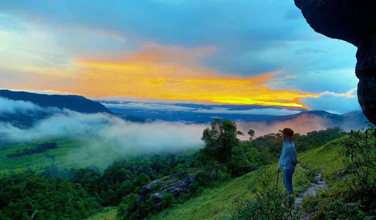 A tourist enjoys the scenery on Knog Phsar mountain in Kampong Speu. Facebook
